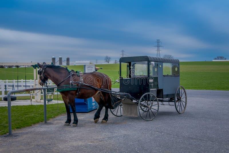 宾夕法尼亚,美国, 2018年4月, 18日:停放的门诺派中的严紧派的多虫的支架室外看法在有用于拉扯的马的一个农场 免版税库存图片