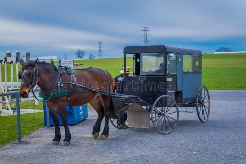 宾夕法尼亚,美国, 2018年4月, 18日:停放的门诺派中的严紧派的多虫的支架室外看法在有用于拉扯的马的一个农场 免版税图库摄影
