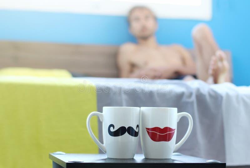 寂寞在两个杯子的谎言在床上和神色早晨茶或咖啡在桌,梦想关于他的缺掉女朋友,周末上 免版税库存图片