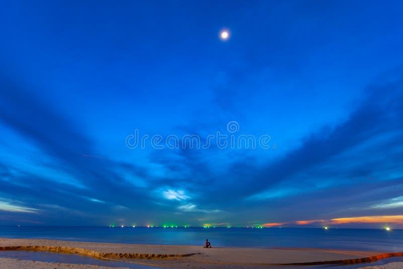 寂寞坐海滩在微明 免版税库存照片