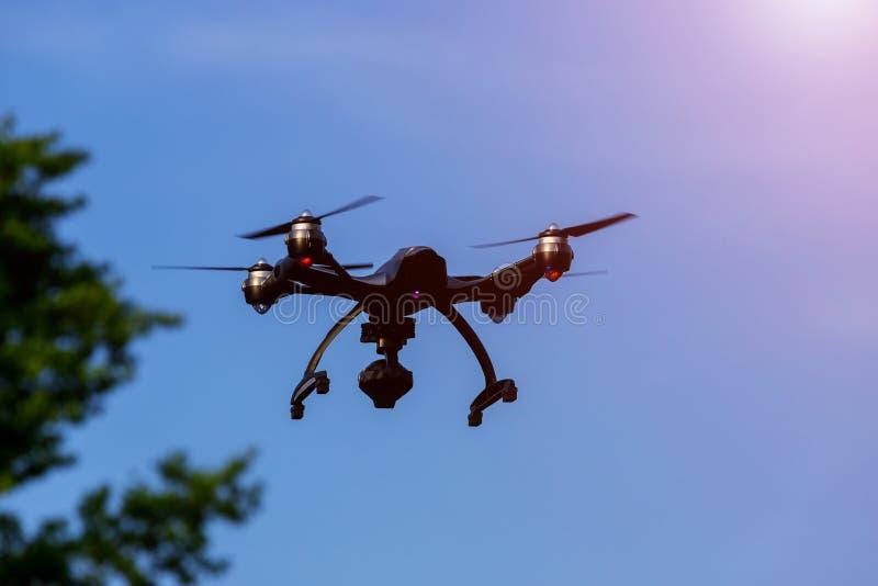 寄生虫或UAV飞行顶上在蓝天 库存图片