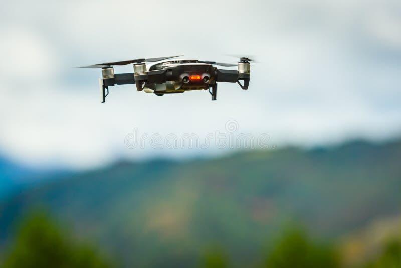 寄生虫有数码相机飞行的quadcopter UAV在天空 免版税图库摄影