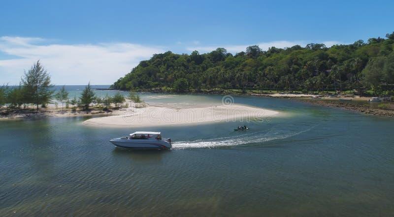 寄生虫被射击快艇和皮船跑在有天空蔚蓝和云彩的在夏天,酸值Mak海岛绿松石海 免版税库存图片