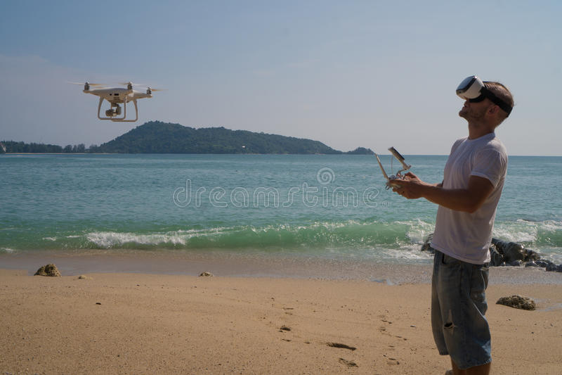 戴寄生虫采取照片和录影在海滩的照相机和虚拟现实眼镜的人 库存照片