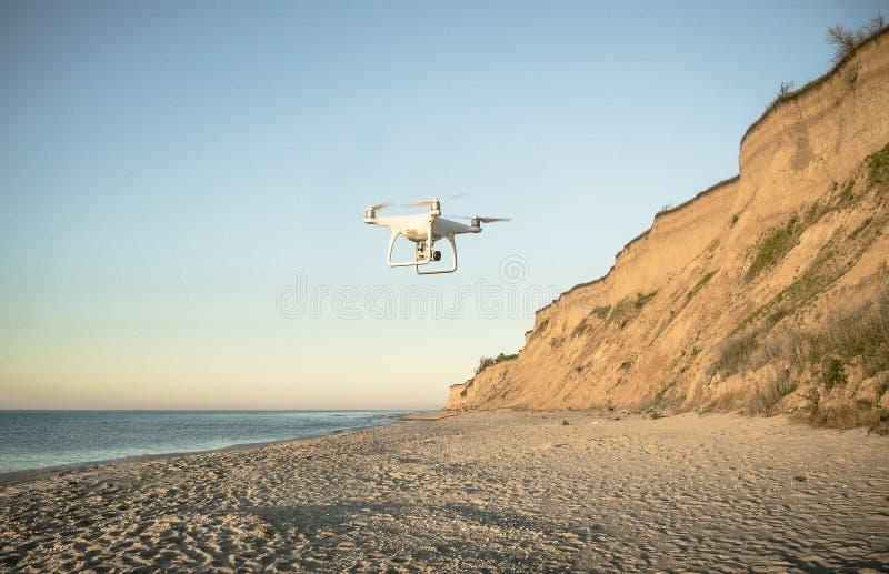 寄生虫飞行在与金黄沙子的离开的童话海滩的,美丽的天空和绿松石在海洋岸浇灌  免版税库存照片
