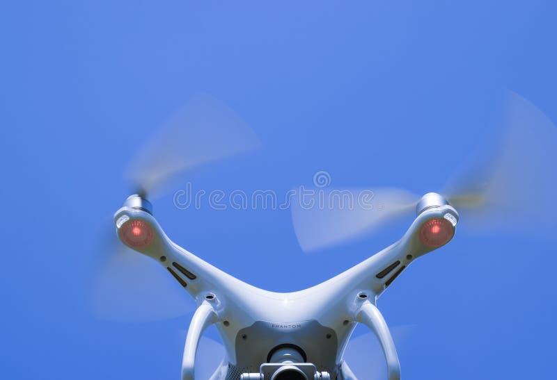 寄生虫DJI幽灵4在飞行中 反对蓝天的Quadrocopter 免版税库存照片