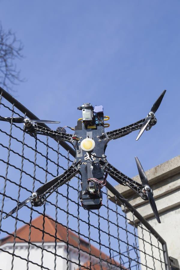 寄生虫quadcopter在篱芭碰撞了在城市公园 免版税库存照片