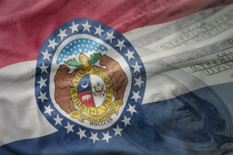 密苏里状态五颜六色的挥动的旗子在美国美元金钱背景的 免版税库存照片
