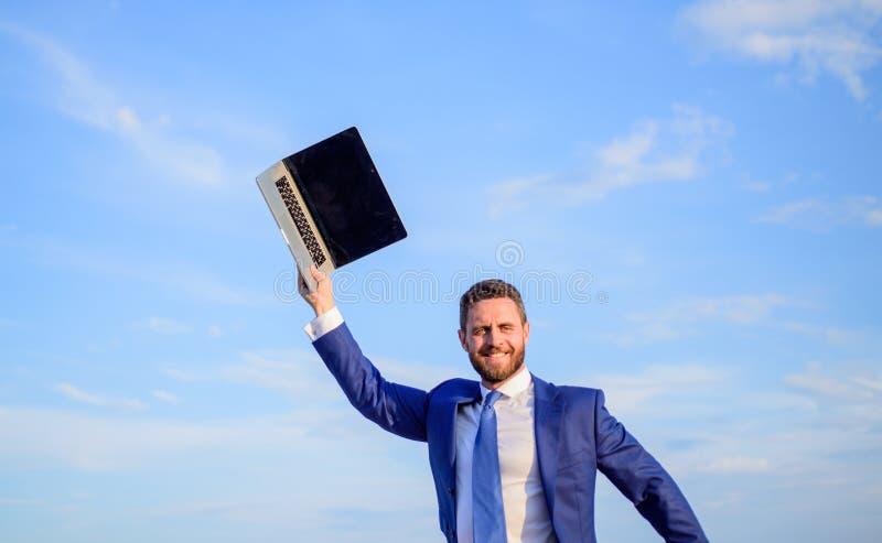 富启示性的创新 商人被启发的企业家感觉强有力去改造世界 人被启发拿着膝上型计算机 图库摄影