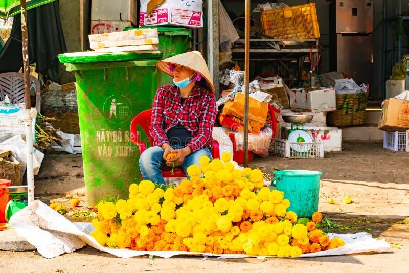 富国岛海岛,越南,2018年2月26日:卖在传统街市上的越南花卖主黄色花 库存照片