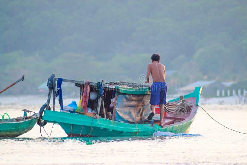 富国岛,越南- 2018年12月:越南渔夫是在他的小绿色家庭小船 免版税库存图片