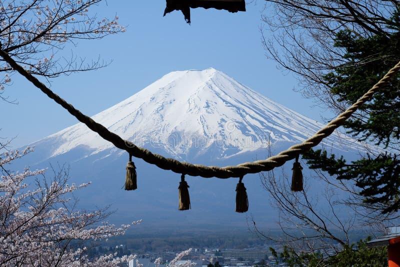 富士山和与Torii一条神圣的绳索在Chureito塔的入口的有蓝天的 图库摄影