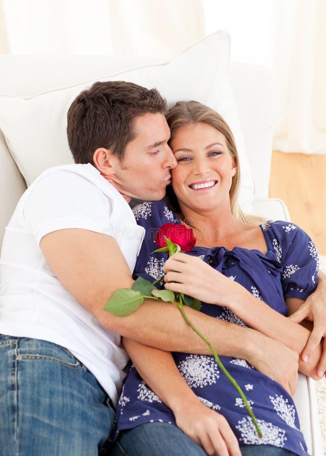 富感情亲吻位于的人沙发妻子的他的 免版税库存照片
