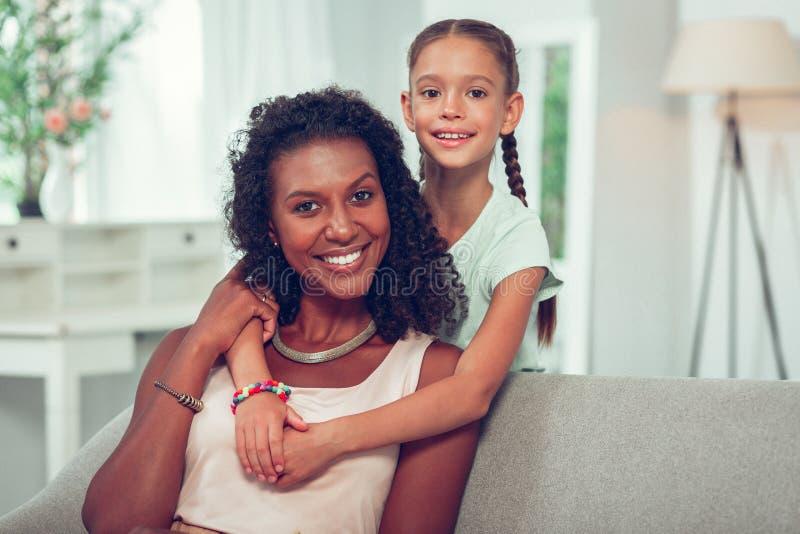 富感情地拥抱美国黑人的发光的妈妈的逗人喜爱的小女儿 免版税库存照片