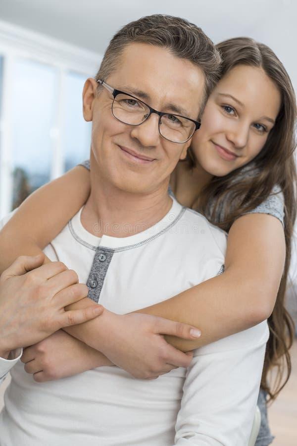 富感情的女孩拥抱的父亲画象从后面在家 免版税库存图片