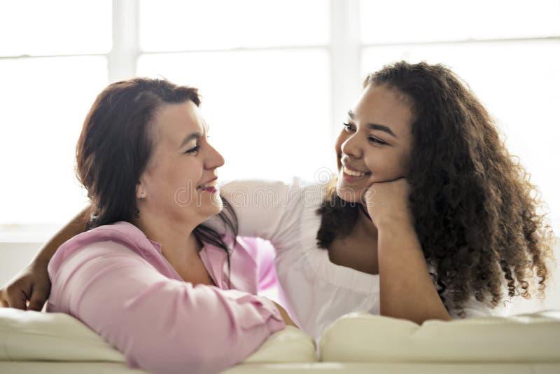 富感情的母亲和女儿坐沙发 免版税库存图片
