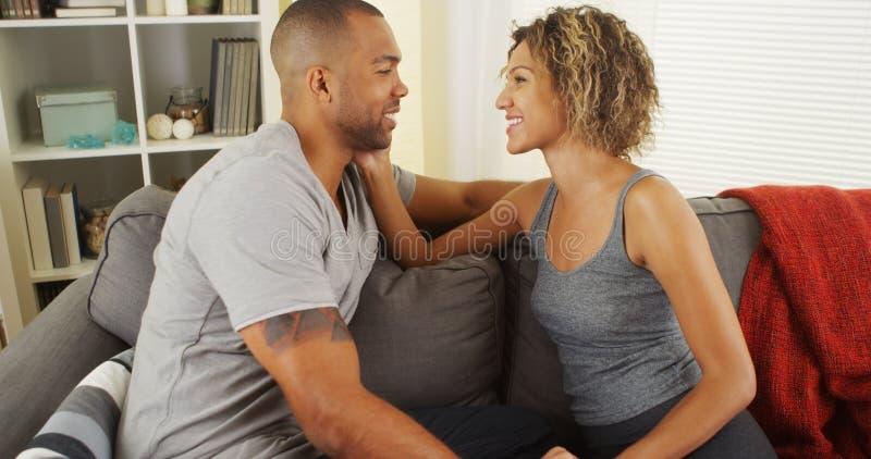 富感情的非洲夫妇谈话在长沙发 库存照片