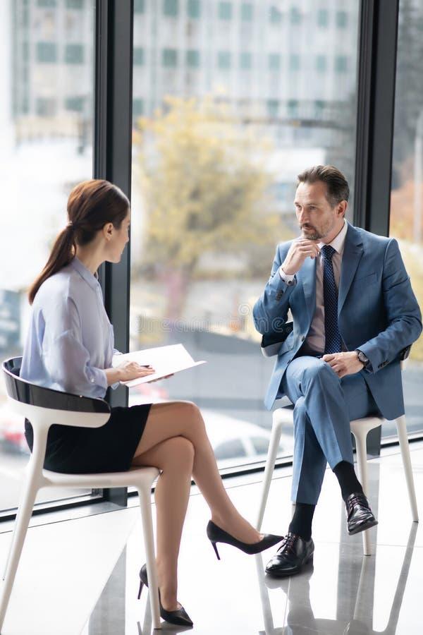 富有企业家与年轻有经验的记者交谈 免版税库存图片