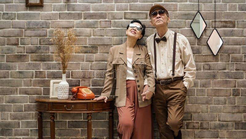 富有的亚洲资深夫妇葡萄酒时尚在豪华房子里 免版税库存图片