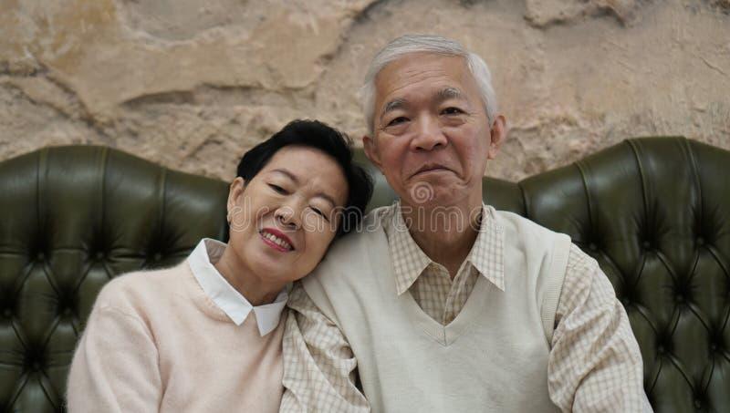 富有的亚裔资深父母在豪华美丽的房子backgrou坐 图库摄影
