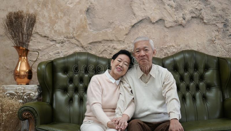 富有的亚裔资深父母在豪华美丽的房子backgrou坐 库存照片