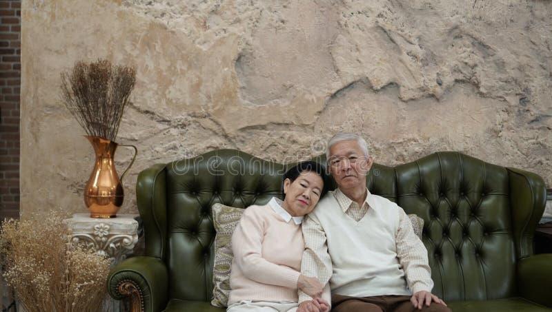 富有的亚裔资深父母在豪华美丽的房子backgrou坐 免版税库存照片