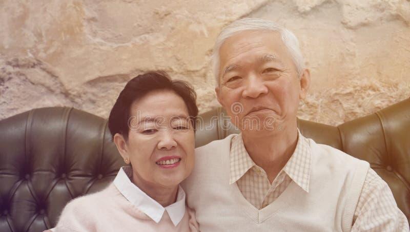 富有的亚裔资深父母在豪华美丽的房子backgrou坐 免版税库存图片