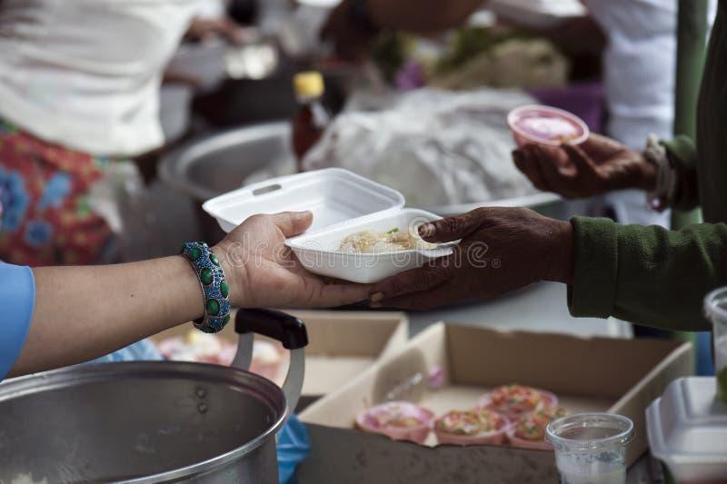 富有的人民给食物贫寒 饥饿概念 免版税库存照片