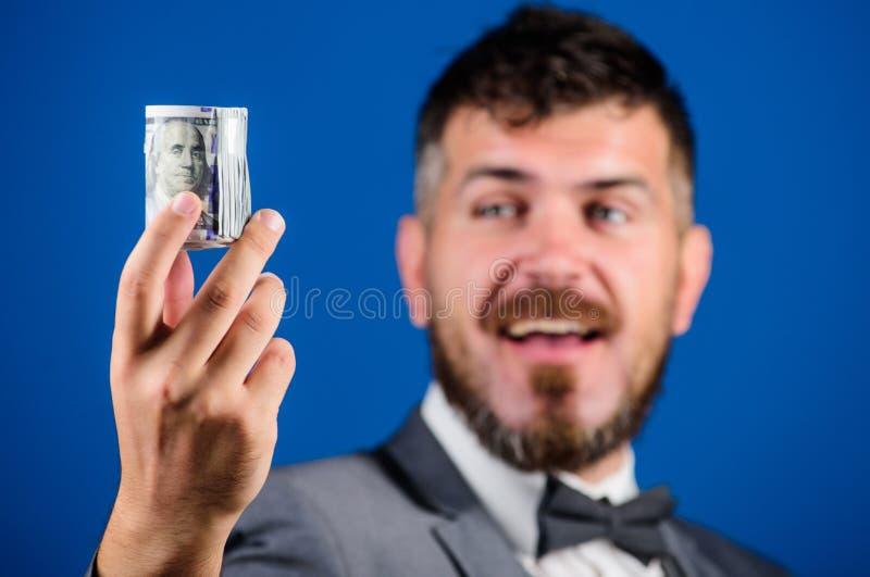 富有的商人举行滚动了金钱 人有胡子的行家举行滚动了美元钞票 人正装提议贿款或 免版税库存图片