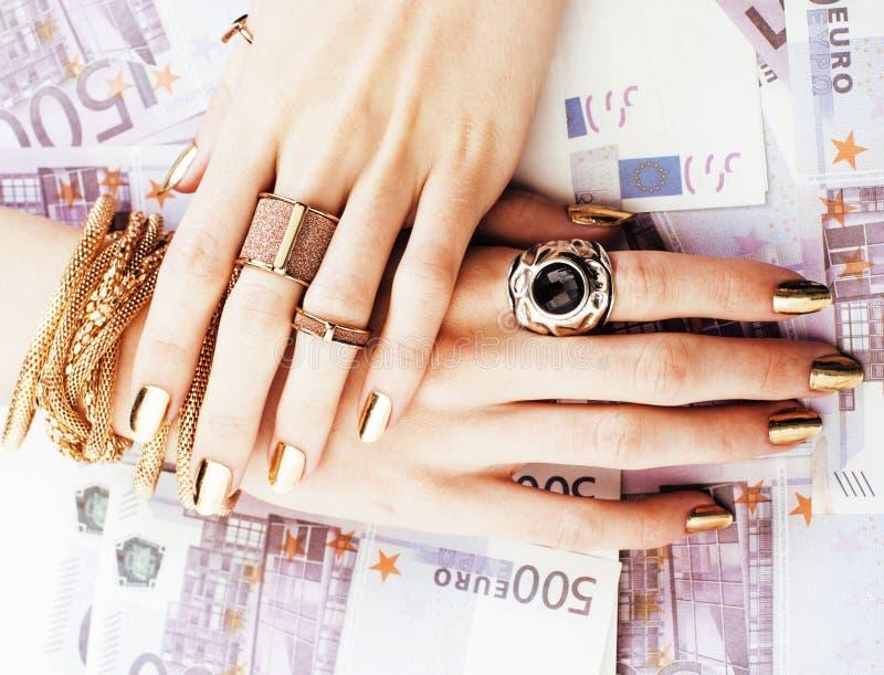 富有的妇女的手有金黄修指甲和许多首饰圆环的在现金欧元 库存图片