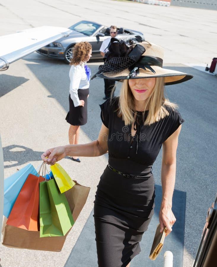 富有的妇女运载的购物袋,当上时 免版税库存图片