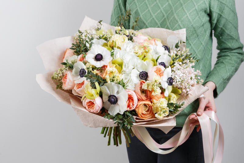 富有的束银莲花属、鸦片、丁香和白色兰花,绿色叶子手中新鲜的春天花束 夏天背景 免版税库存照片