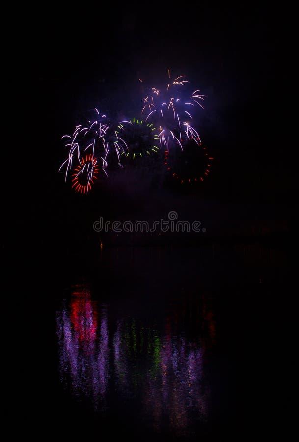 富有的烟花红色和绿色圆环在布尔诺的水坝表面的有反射的湖表面上  库存图片