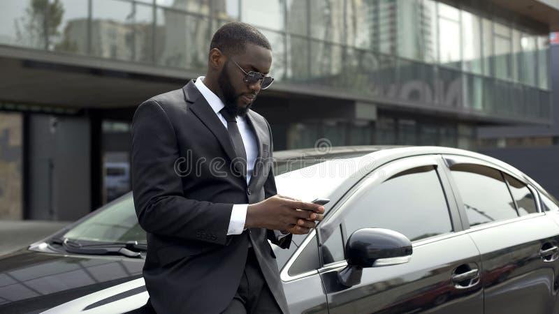 富有的美国黑人的在要做生意的办公楼附近的人等待的伙伴 免版税库存照片