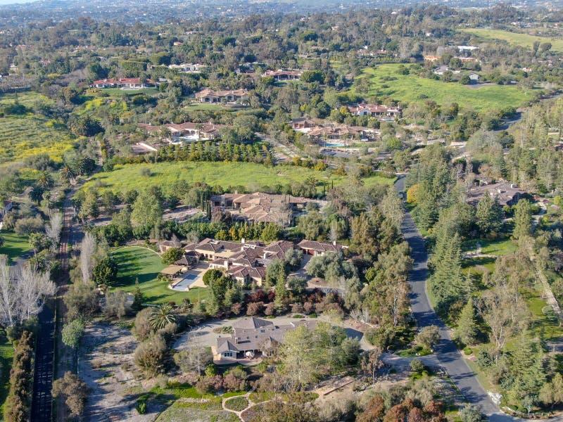 富裕的乡下区域鸟瞰图与豪华别墅的与游泳场,围拢由森林和山谷 免版税库存图片