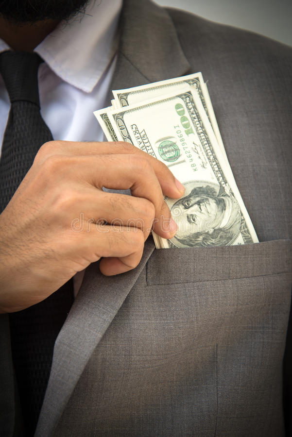 富裕英俊 年轻人特写镜头投入金钱的formalwear的 免版税图库摄影