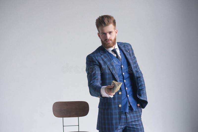 富裕英俊 年轻人特写镜头延长金钱的formalwear的,当站立反对灰色背景时 免版税图库摄影