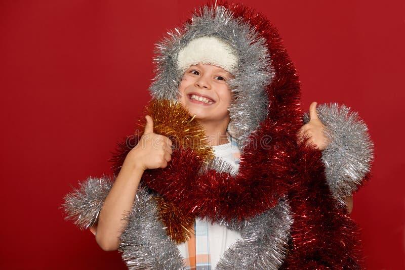 寒假圣诞节概念-获得圣诞老人的帽子的男孩在红色的乐趣 免版税库存照片