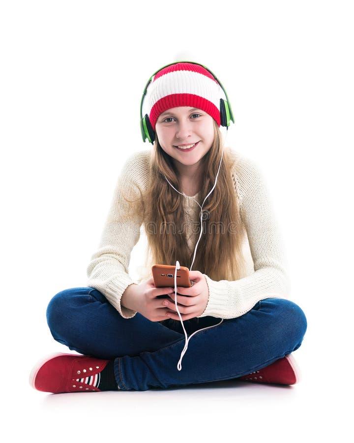 寒假圣诞节的幸福 少年概念-红色帽子的微笑的年轻女人有智能手机的和 免版税库存照片