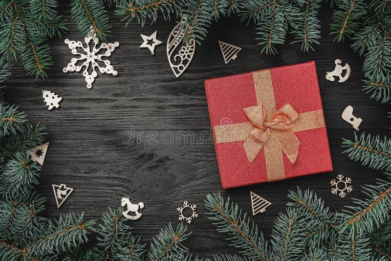 寒假墙纸在黑背景的 红色礼物和木玩具 冷杉木 免版税图库摄影