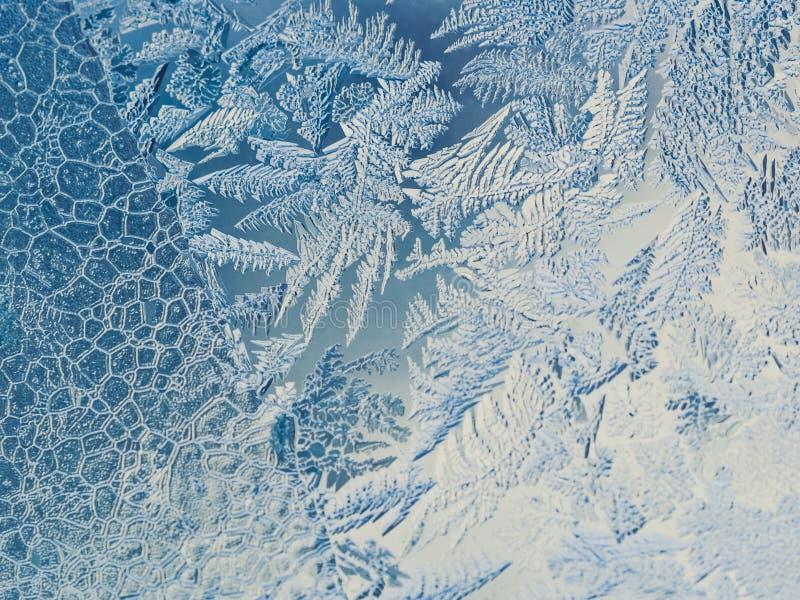 寒假季节幻想世界概念:与拷贝空间的蓝色冷淡的玻璃窗天然冰样式的宏观图象 库存照片