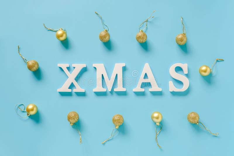 寒假构成 发短信给从白色信件和圣诞装饰金黄球的Xmas在蓝色背景 库存照片