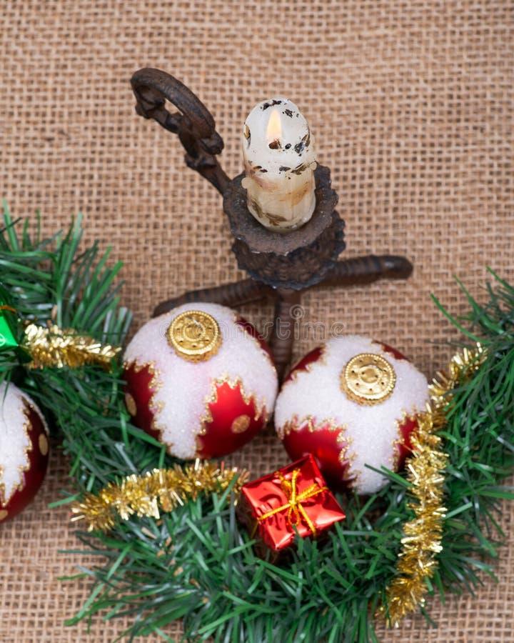 寒假装饰:圣诞树球、礼物装饰、闪亮金属片诗歌选和燃烧的蜡烛粗麻布 图库摄影