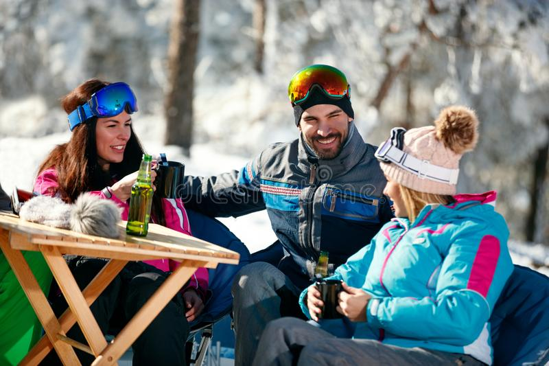 寒假-喝在断裂的朋友啤酒在滑雪胜地 免版税库存图片