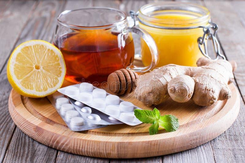 寒冷、医学和蜂蜜的热的茶在木桌上 库存照片