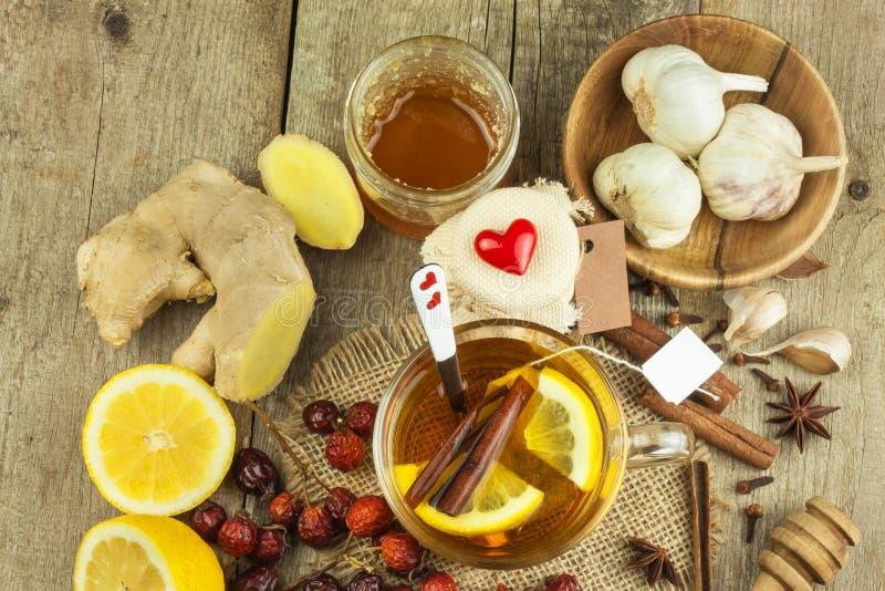 寒冷和流感的自然治疗 姜柠檬蜂蜜大蒜和野玫瑰果茶反对流行性感冒 寒冷的热的茶 家庭药房 免版税库存图片