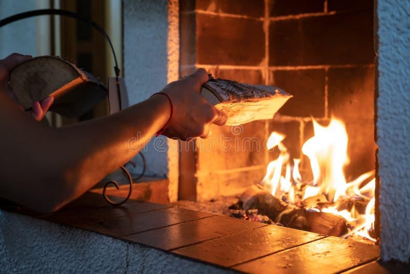 寒冷的冬日,手把柴火放在燃木壁炉里 温暖舒适的房子 免版税库存图片