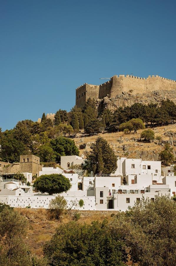 对一个小的村庄Lindos的一个看法白色房子位于罗得岛的有很多,希腊的小山的 在backgrou的一座老城堡 免版税库存照片