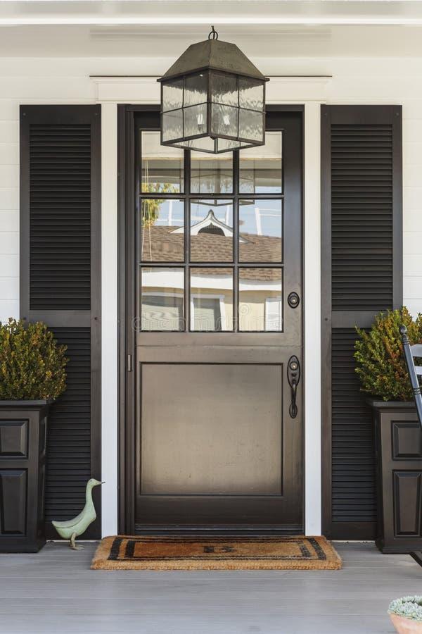 对一个房子的黑前门有门廊的 免版税库存图片