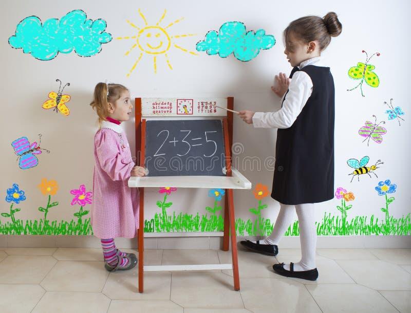 对一个更加年轻的孩子的小女孩教的数学 库存照片